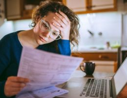Woman-going-through-bills,-looking-worried-cm