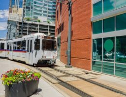 Light-rail-train-traveling-through-a-sun-filled-city-cm