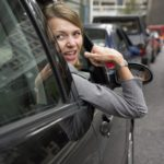 Woman-Sitting-in-Her-Car-in-a-Traffic-Jam-Looking-Back-and-Gesturing-With-Frustration-cm