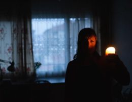 Woman-with-candle-at-home-because-of-power-cut-cm