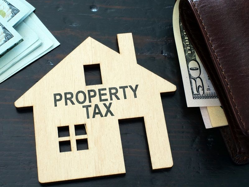 Property-tax-sign-on-a-house-model.--cm