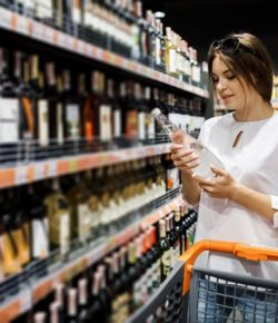 Young-pretty-girl-is-shopping-in-a-big-store.-The-girl-buys-groceries-at-the-supermarket.-Girl-chooses-drinks-cm