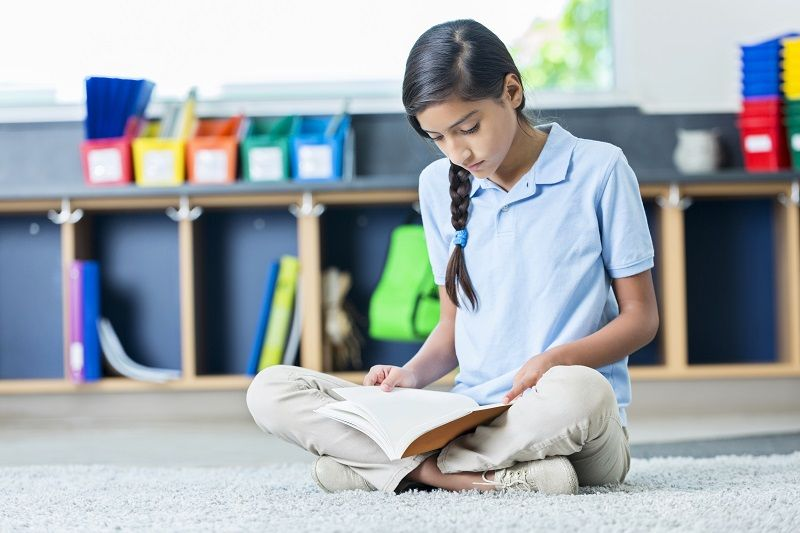 Hispanic-middle-school-student-reads-book-in-classroom-cm
